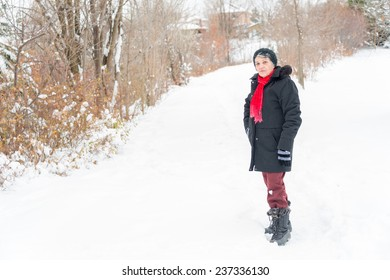 Hispanic senior visiting Canada and enjoying, having fun and having her portrait taken  in the first snow of her life at about 74 years old