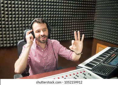 Hispanic sound engineer gesturing ok sign to start the show at radio station