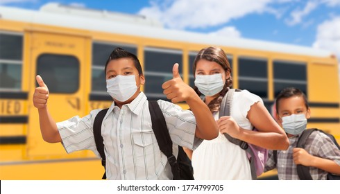 Hispanic Students Near School Bus Wearing Face Masks.