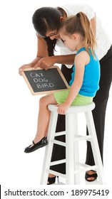 Hispanic teacher helps little girl with first reading words on a small chalk board. Studio shot, isolated on white background.