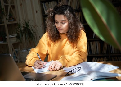 Hispanic teen girl college student study from home office making notes doing homework in sunny room. Latin smart teenage school pupil learning online on laptop sit at desk. Distance elearning concept.