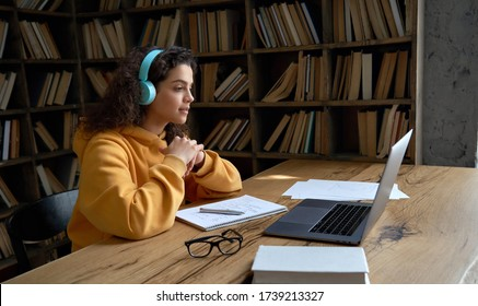 Hispanic teen girl, latin young woman school college student wear headphones learn watching online webinar webcast class looking at laptop elearning distance course or video calling remote teacher.
