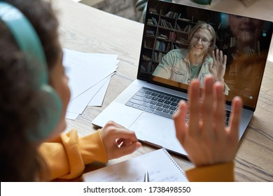 Hispanic teen girl school college student distance learning waving hand studying with online teacher on laptop screen. Elearning zoom video call, videoconference class with tutor. Over shoulder view. - Shutterstock ID 1738498550