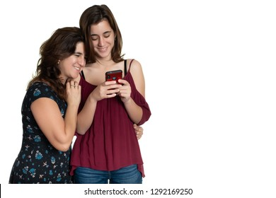 Hispanic teenage girl and her affectionate mother looking at a smartphone and smiling - Isolated on white