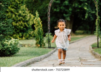 Hispanic toddler girl two years old in white polka-dot shirt and blue denim shorts running on track of garden or park.