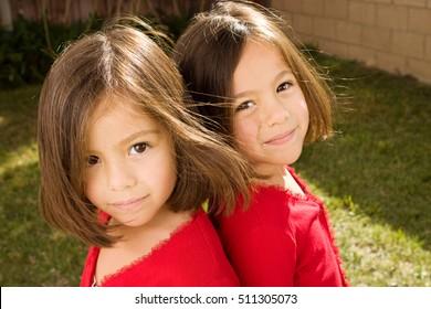 Hispanic twin sisters.