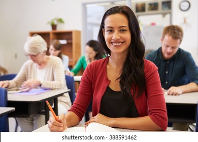 Hispanic woman at an adult education class looking to camera