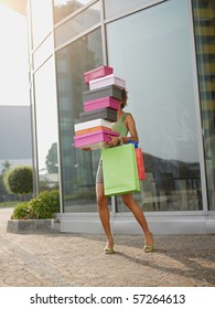 hispanic woman balancing stack of shoe boxes out of shopping center. Vertical shape, full length, copy space