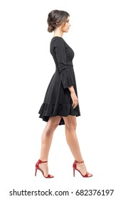 Hispanic woman in black dress and red high heels sandals walking looking ahead side view. Full body length portrait isolated on white background.