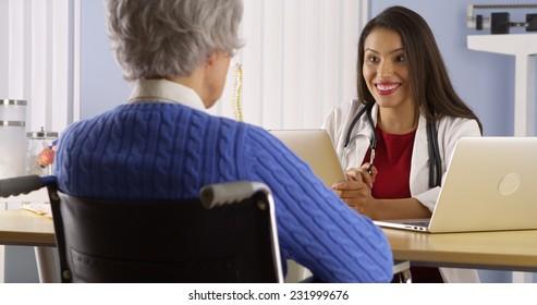 Hispanic woman doctor talking with elderly patient