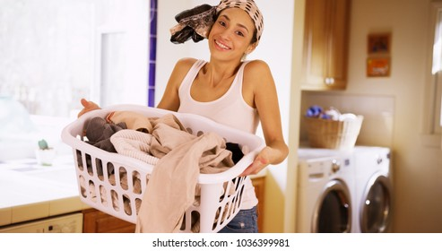 A Hispanic woman does her laundry as she poses for a portrait