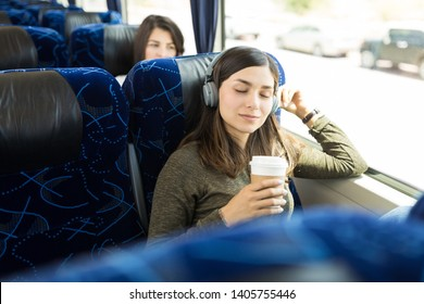 Hispanic woman enjoying music and coffee while sitting in bus