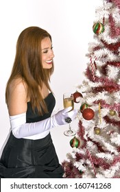 A Hispanic woman in an evening gown and white gloves, holding a glass of champagne, while looking at a decorated Christmas tree.