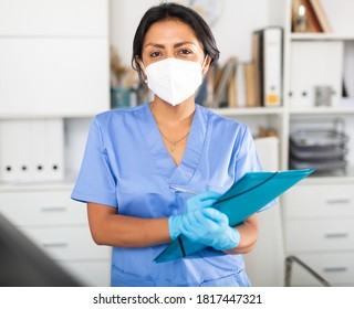 Hispanic woman general practitioner in blue uniform and face mask standing in clinic, filling out clipboard with medical records