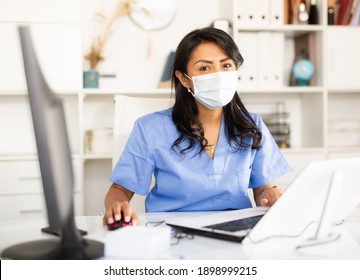 Hispanic woman general practitioner wearing medical mask working with case histories on laptop in modern office.