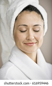 Hispanic woman with hair wrapped in towel