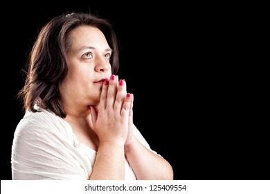 Hispanic woman with her hands folded in prayer and eyes open against a black background with space for custom text