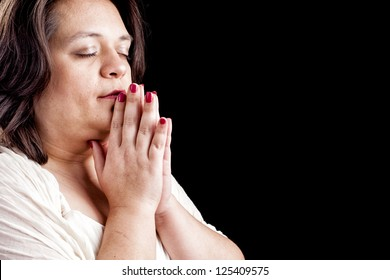 Hispanic woman with her hands folded in prayer and eyes closed against a black background with space for custom text