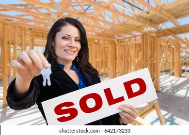 Hispanic Woman With Keys and Sold Sign On Site Inside New Home Construction Framing.
