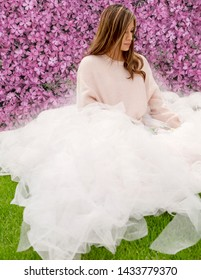 hispanic woman in large fashion ballet skirt in front of pink floral wall