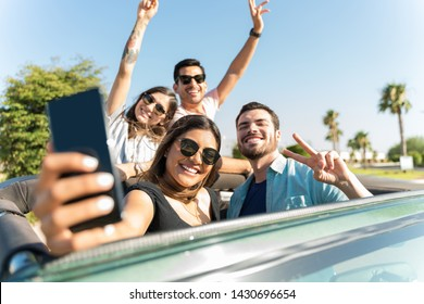 Hispanic woman making memories with friends on smartphone in SUV during roadtrip