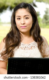 A Hispanic woman in the park with her laptop computer.