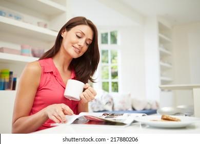 Hispanic Woman Reading Magazine In Kitchen At Home