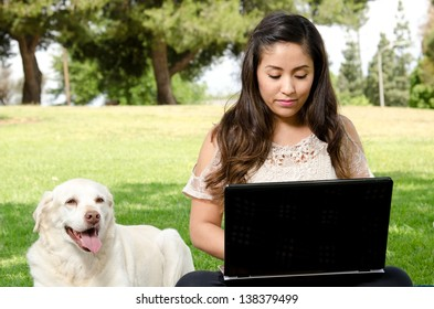 a Hispanic woman sitting in the park with her dog and her computer.