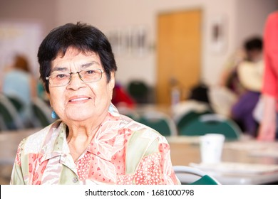 Hispanic woman smiling in a busy senior center