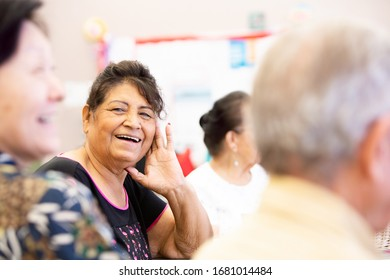 Hispanic woman smiling and talking in a senior center