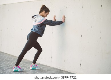 Hispanic woman stretching before her running workout