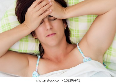 Hispanic woman suffering from a strong headache or depression and laying n bed