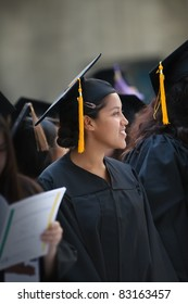 Hispanic woman wearing graduation hat and gown