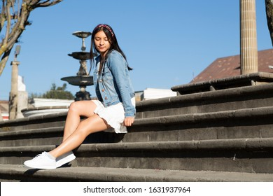 Hispanic woman in white dress sitting on stone bleachers smiling - Quetzaltenango Theater Guatemala - comfortable woman in the street