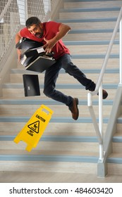 Hispanic worker carrying files falling on wet stairs