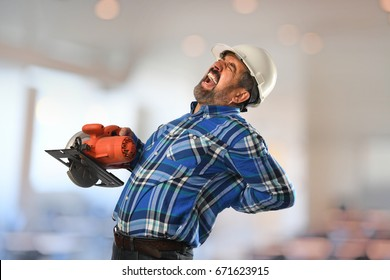 Hispanic worker experiencing back injury while working with circular saw