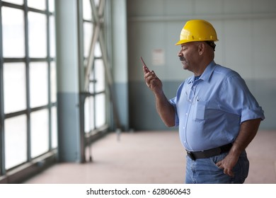 Hispanic worker text messaging on cell phone