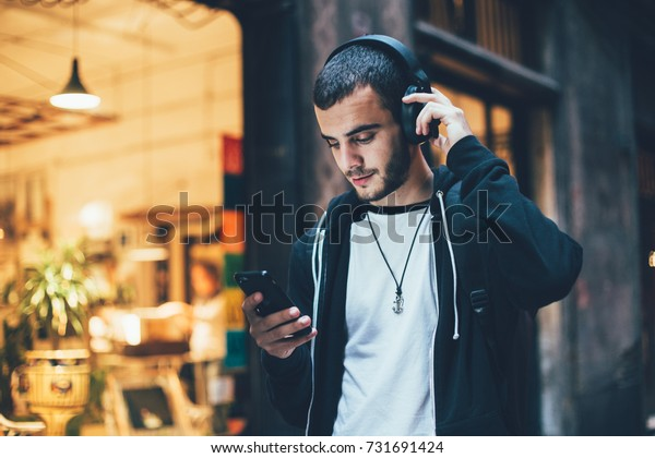 Hispanic young attractive man stands in dark street in front of shop, changes songs and tracks on smartphone, listens to music in wireless headphones. Hipster with slight beard