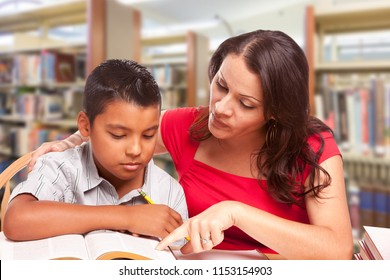 Hispanic Young Boy and Famle Adult Studying At Library.