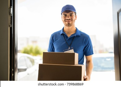 Hispanic young delivery man bringing some packages to a house and smiling