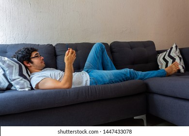 Hispanic young man with clear brown skin wearing glasses using smarthphone on a couch