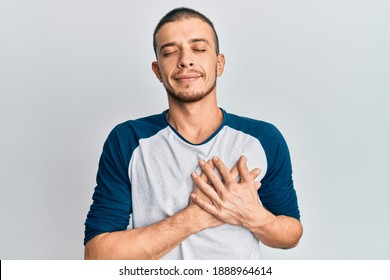 Hispanic young man wearing casual clothes smiling with hands on chest with closed eyes and grateful gesture on face. health concept.