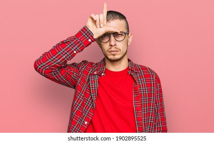 Hispanic young man wearing casual clothes making fun of people with fingers on forehead doing loser gesture mocking and insulting.