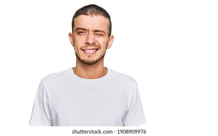 Hispanic young man wearing casual white t shirt winking looking at the camera with sexy expression, cheerful and happy face.