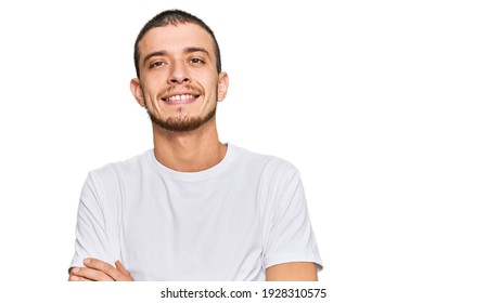 Hispanic young man wearing casual white t shirt happy face smiling with crossed arms looking at the camera. positive person.