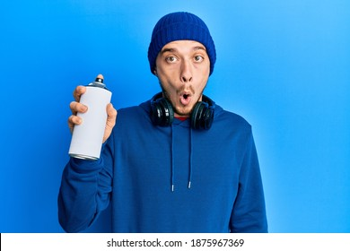 Hispanic young man wearing sweatshirt holding graffiti spray scared and amazed with open mouth for surprise, disbelief face