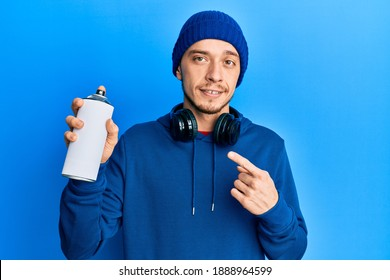 Hispanic young man wearing sweatshirt holding graffiti spray smiling happy pointing with hand and finger