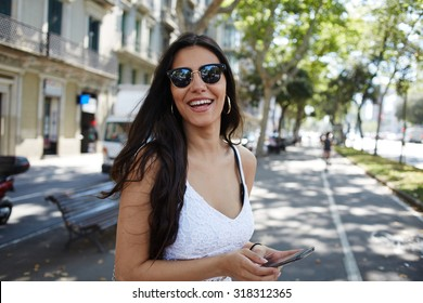 Hispanic young woman enjoying summer walk in the city feeling joy and happy while smiling to the camera, attractive female laughing just received good message on mobile phone while strolling outdoors