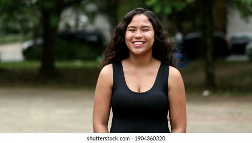 Hispanic young woman smiling to camera at park, casual real people series