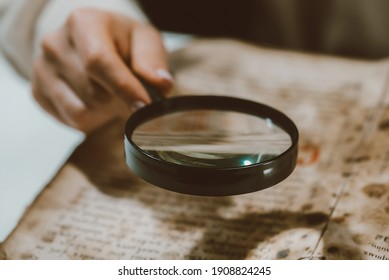 Historian scientist reading antique book with magnifying glass. Translation of religious literature. Manuscript with ancient writings. Treasures of the past. Museum piece - Shutterstock ID 1908824245